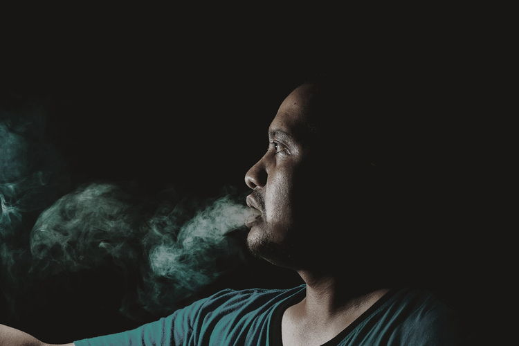 Mid Adult Man Emitting Smoke Against Black Background