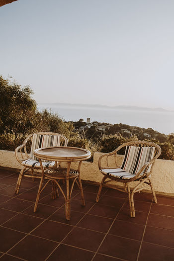 Empty chairs and table by sea against clear sky
