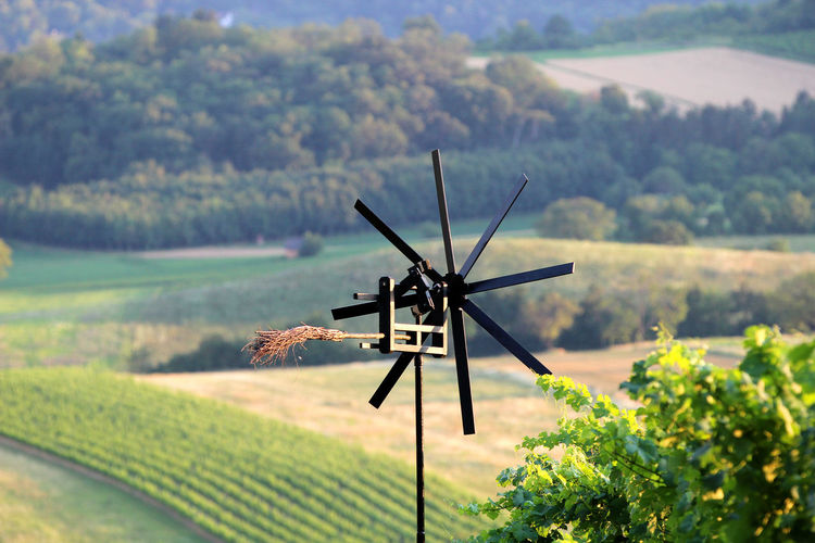Traditional windmill on field against trees