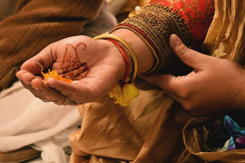 Cropped hand of groom holding petal during wedding ceremony