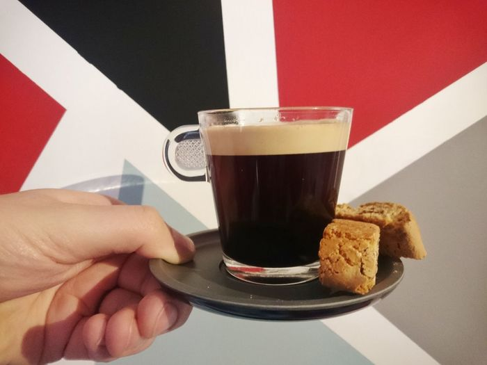 Cropped Hand Of Person Holding Black Coffee With Biscotti In Plate