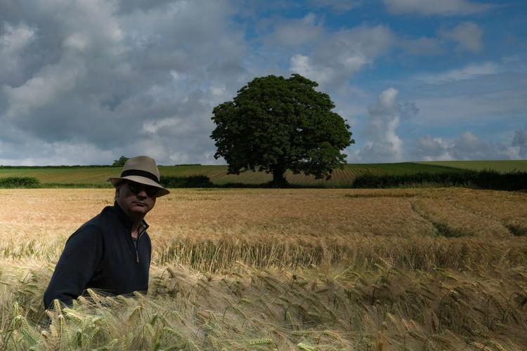 Man wearing hat standing amidst crops on field