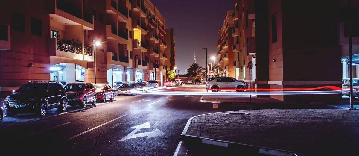 Cars on city street by buildings at night