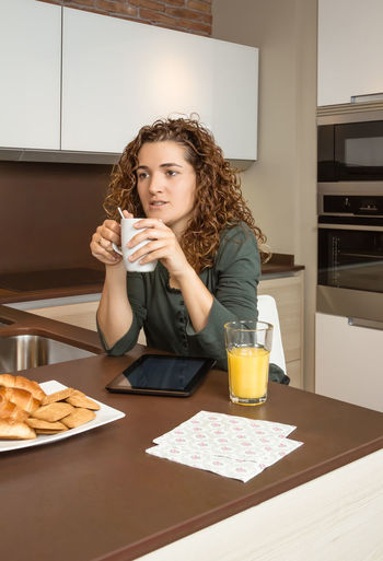 Tired young girl with cup of coffee and digital tablet at home breakfast Family Fruit Girlfriend Thirties Relaxing Husband Boyfriend 30s Wife Relationship Adult Lifestyle Interior Love Cup Caucasian Healthy Two Coffee Glass Orange Girl Juice Meal Drink Together Young Woman Kitchen Man Indoors  Food Morning Technology Newspaper Digital Tablet News Read Problems Bored Tired Serious Male Home People Female Couple Breakfast
