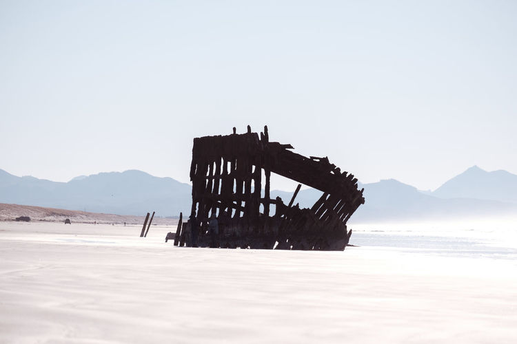 Lifeguard hut on sea shore against clear sky