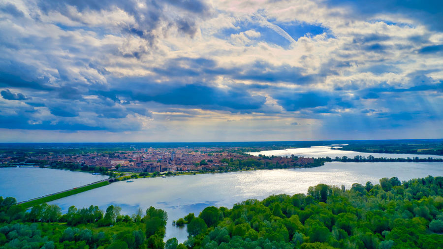 Italy, Mantua: historical city of Mantua surrounded by 3 lakes Drone  Drone Photography Mavic 2 Pro Mavic Rays Of Light Lake UNESCO World Heritage Site Unesco World Heritage Unesco Sun Rays Cloudy Cloud - Sky Forest Outdoors Landscape Scenics Horizon Over Land From A Distance From Above  Reflection Mantova Mantua Italy Sky Scenics - Nature Beauty In Nature Water Nature Tranquil Scene Plant Tranquility Tree Sea Day No People Idyllic Environment Horizon Land Nobody