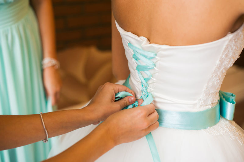 Close-up of woman assisting bride for getting dressed