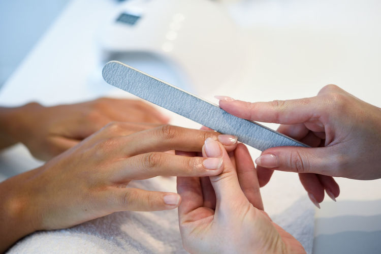 Close-up of beautician cutting woman nail