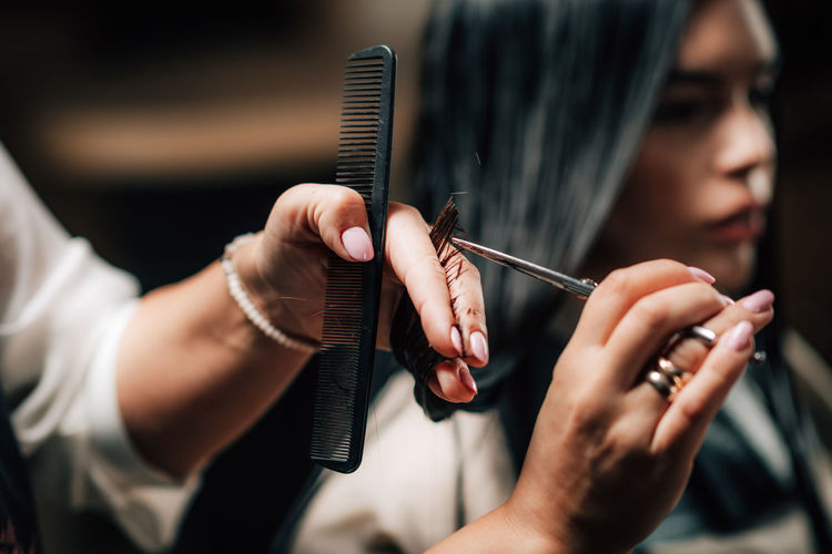 Cropped hands of hairdresser cutting woman hair in salon
