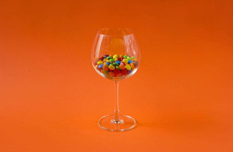 Close-up of wine glass against orange background