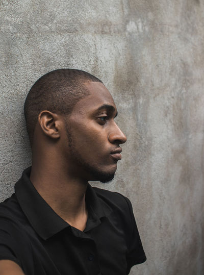 Thoughtful young man against wall