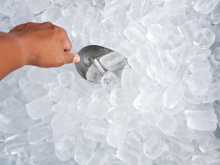 Close-Up Of Hand Scooping Ice Cubes