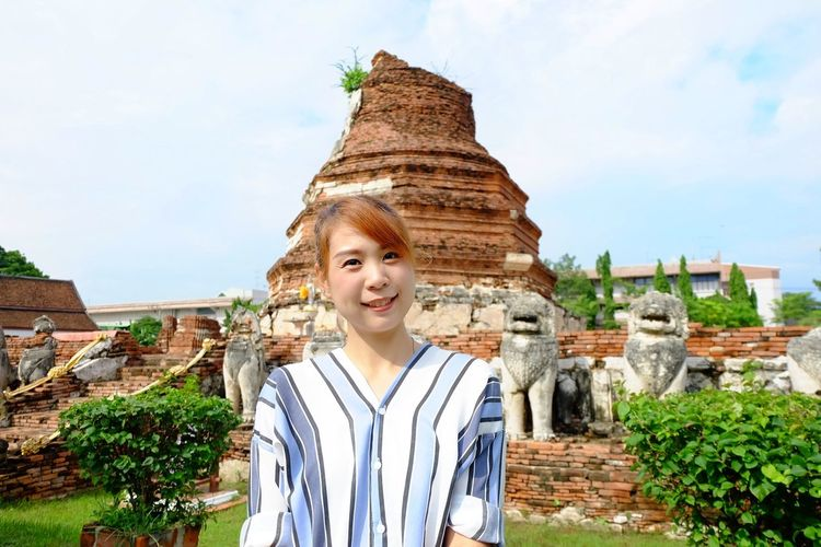 Portrait of young woman standing at wat thammikarat against sky