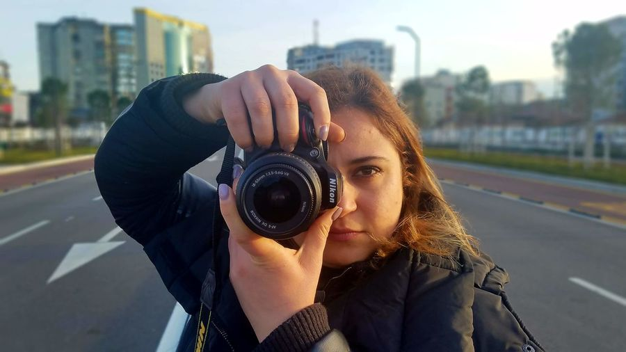 Cityscape streetphotography buildings people photography peo EyeEmSelect Cityscape Streetphotography Buildings People Photography Human Hand Human Body Part Blonde Girl Shooting Photos Shooting Day Camera - Photographic Equipment Looking At Camera Portrait Of A Woman This Is Queer