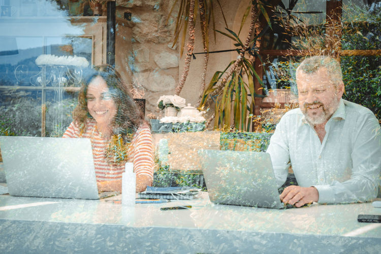Mature man and woman working from home sitting seen through window