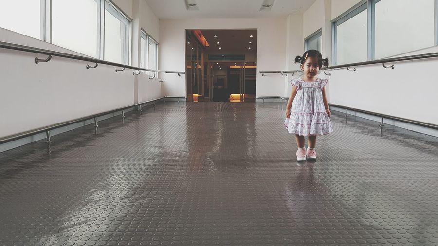 Portrait of cute girl standing at hallway in building
