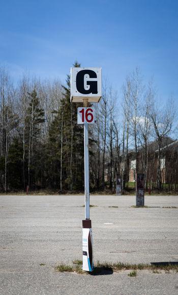 Road sign on roadside against blue sky