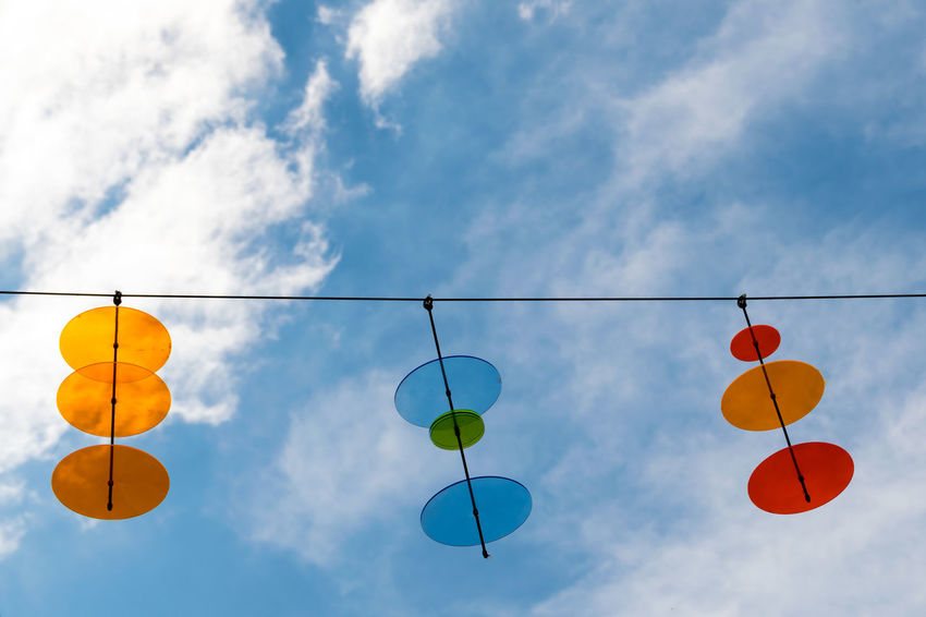 Minimal decoration to transform sunrays into colourful spotlights. Balloon Blue Cable Cloud Cloudy Color Colorful Colors Day Decoration Disc Disk Disks Geometric Shape Look Up Look Up And Thrive Minimalism Modern Multi Colored Orange Color Outdoors Red Sky Transparent Yellow