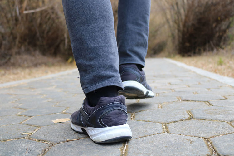 Low section of person walking on footpath