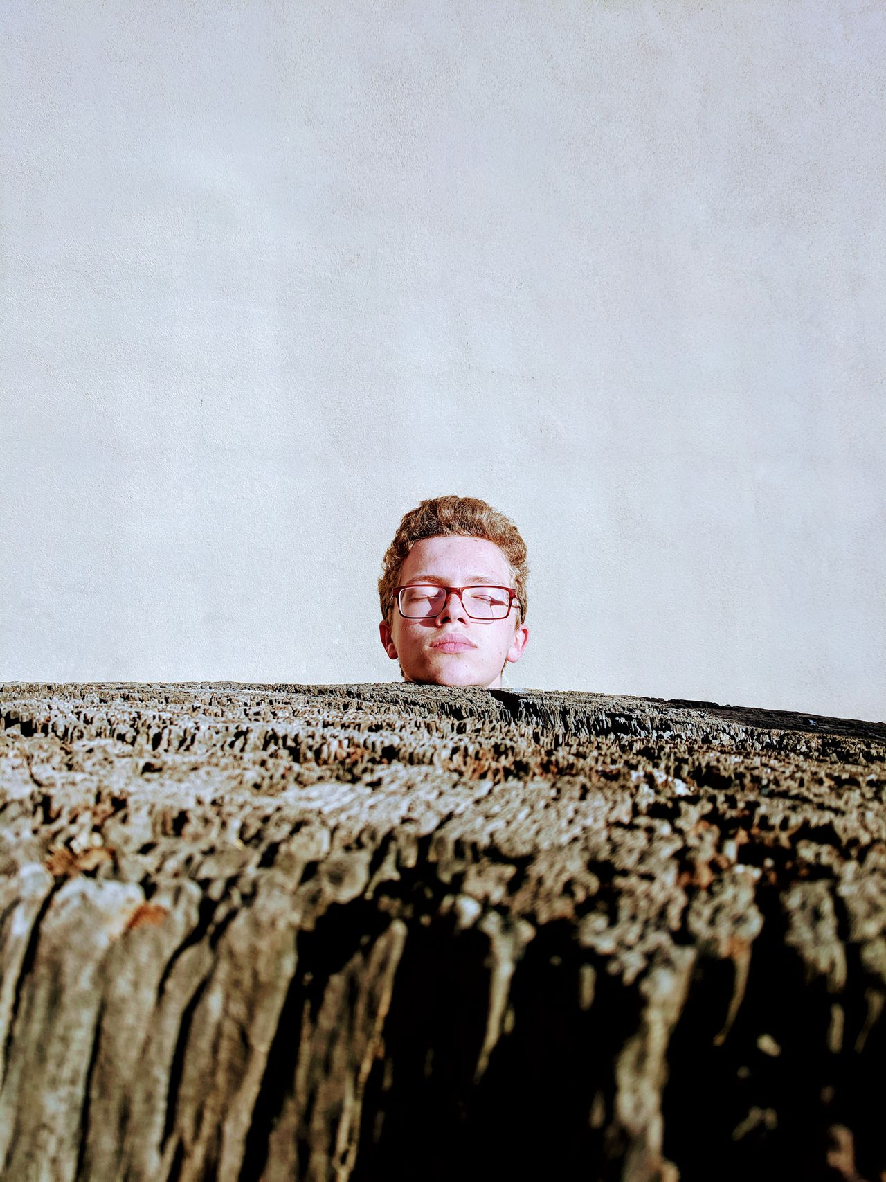Teenage boy with eyes closed standing by wood against wall