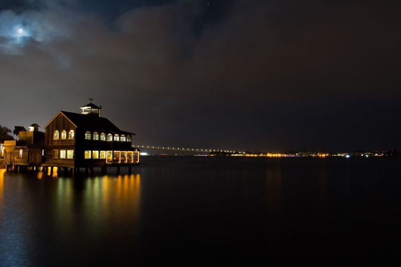 Illuminated building by sea against sky at night