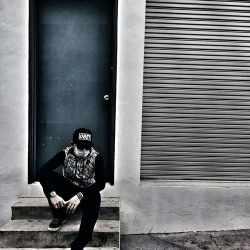Man wearing surgical mask sitting on steps at entrance of building