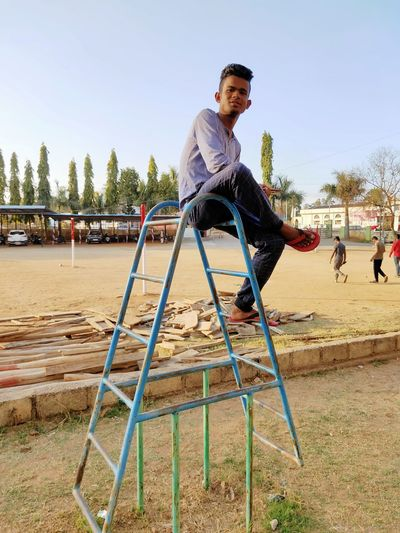 Full length of young man sitting on play equipment outdoors