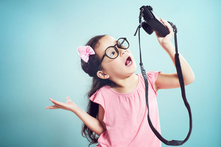 Girl taking selfie with camera while standing against turquoise background