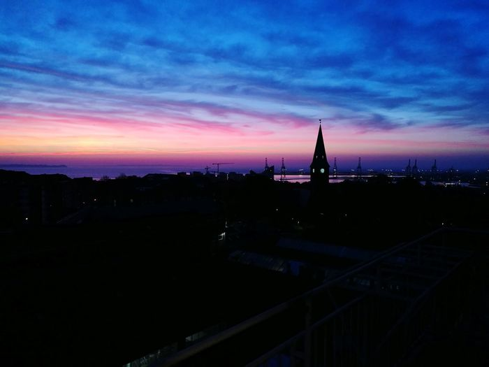 Silhouette buildings against sky at dusk