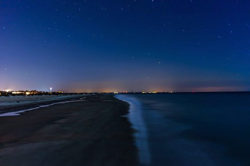 Illuminated landscape against blue sky