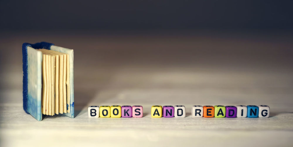 Close-up of book by multi colored cubes on table