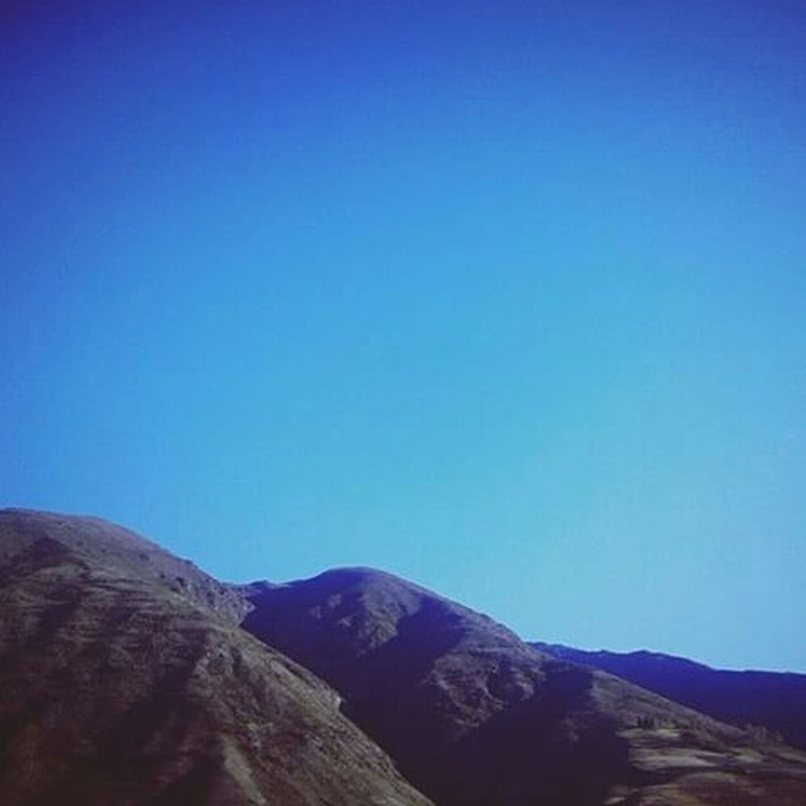 clear sky, copy space, blue, mountain, tranquil scene, tranquility, scenics, mountain range, beauty in nature, nature, landscape, idyllic, non-urban scene, low angle view, outdoors, day, remote, no people, geology, physical geography