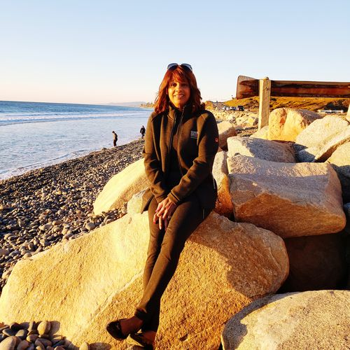 Portrait of woman sitting on rocks at beach against sky