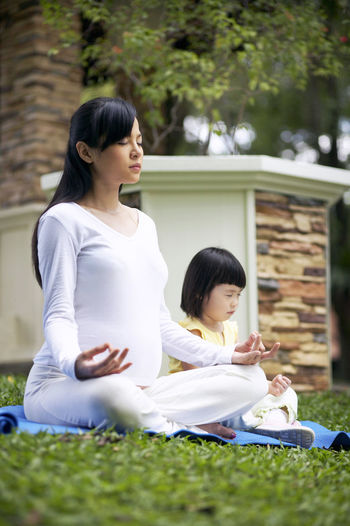 Mother and daughter meditating in park