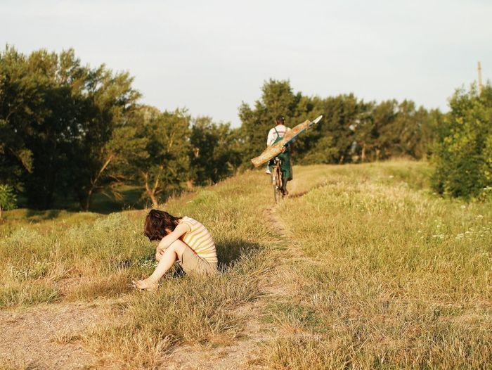 Full Length Of Woman Sitting On Grassy Field