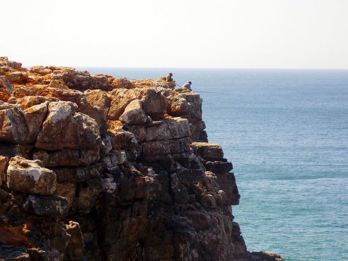 Men on cliff fishing in sea against clear sky