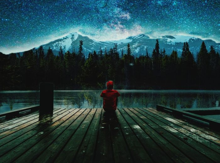 Rear view of man sitting on pier over lake against sky at night