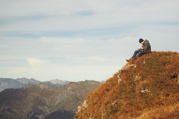 Man Sitting At Mountain Peak Against Sky
