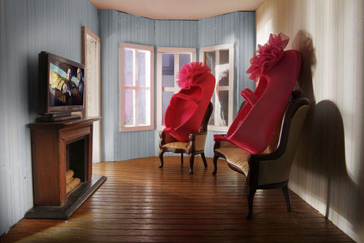 Large shoes on chairs with television in living room