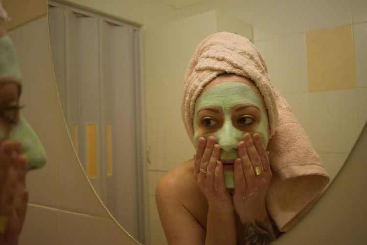 Young woman analyzing facial mask in mirror