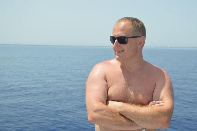 Man wearing sunglasses on sea against sky