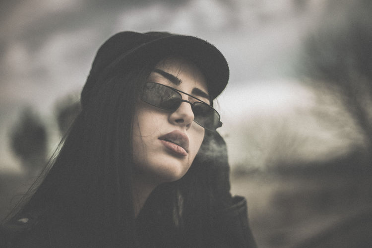 Close-up portrait of young woman smoking while sitting outdoors