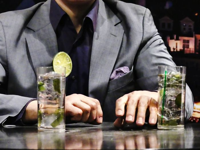 Close-up of man drinking glasses on table