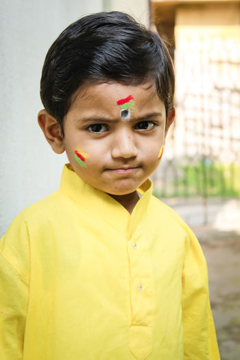 Portrait of cute boy wearing yellow traditional clothing outside house