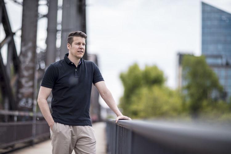 Handsome Young Man Standing On Bridge