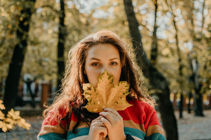 Portrait of young woman holding plant against tree