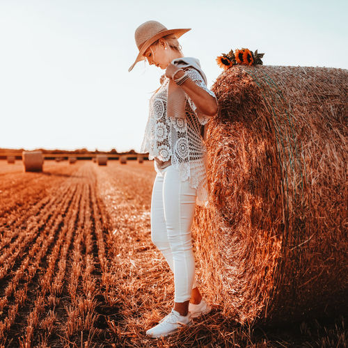 Woman wearing straw hat standing on field against sky during sunset