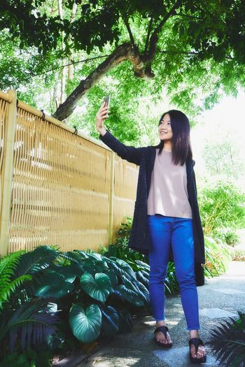 Asian girl using smartphone to selfie in garden. Smiling Happiness Tree Casual Clothing Standing Young Women Outdoors Day Smartphone Technology Connection Social Network Communication Modern Life Video Call lLifestyles lLeisure Activity Relaxing Girl Portrait Mix Yourself A Good Time