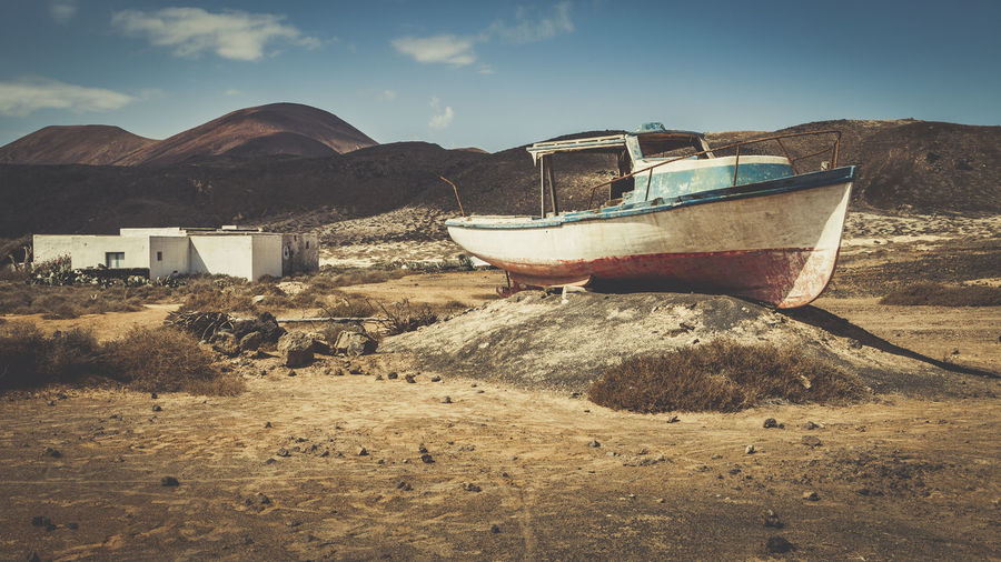 Boat moored on beach against sky