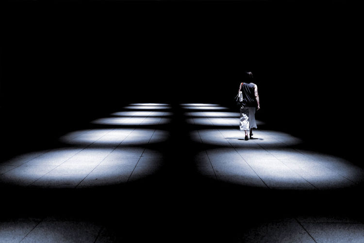 Rear view of woman walking in illuminated corridor